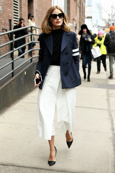 STREET STYLE: Fashion blogger Olivia Palermo, wearing white culotte pants with a navy blazer attends the Tibi fashion show on February 14, 2015 in New York City